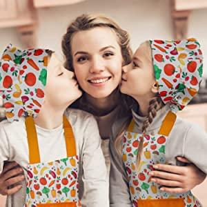 Kids Wearing RiseBrite Kids Vegetable Apron And Chef Hat Kissing Mother