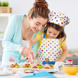 Mother And Daughter Wearing Polka Dot Apron And Chef Decorating Cupcakes