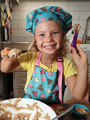 Young Girl In RiseBrite Pink Heart And Light Blue Apron And Chef Hat Scooping Batter