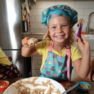 Young Girl Baking While Wearing RiseBrite Pink Heart Apron And Chef Hat